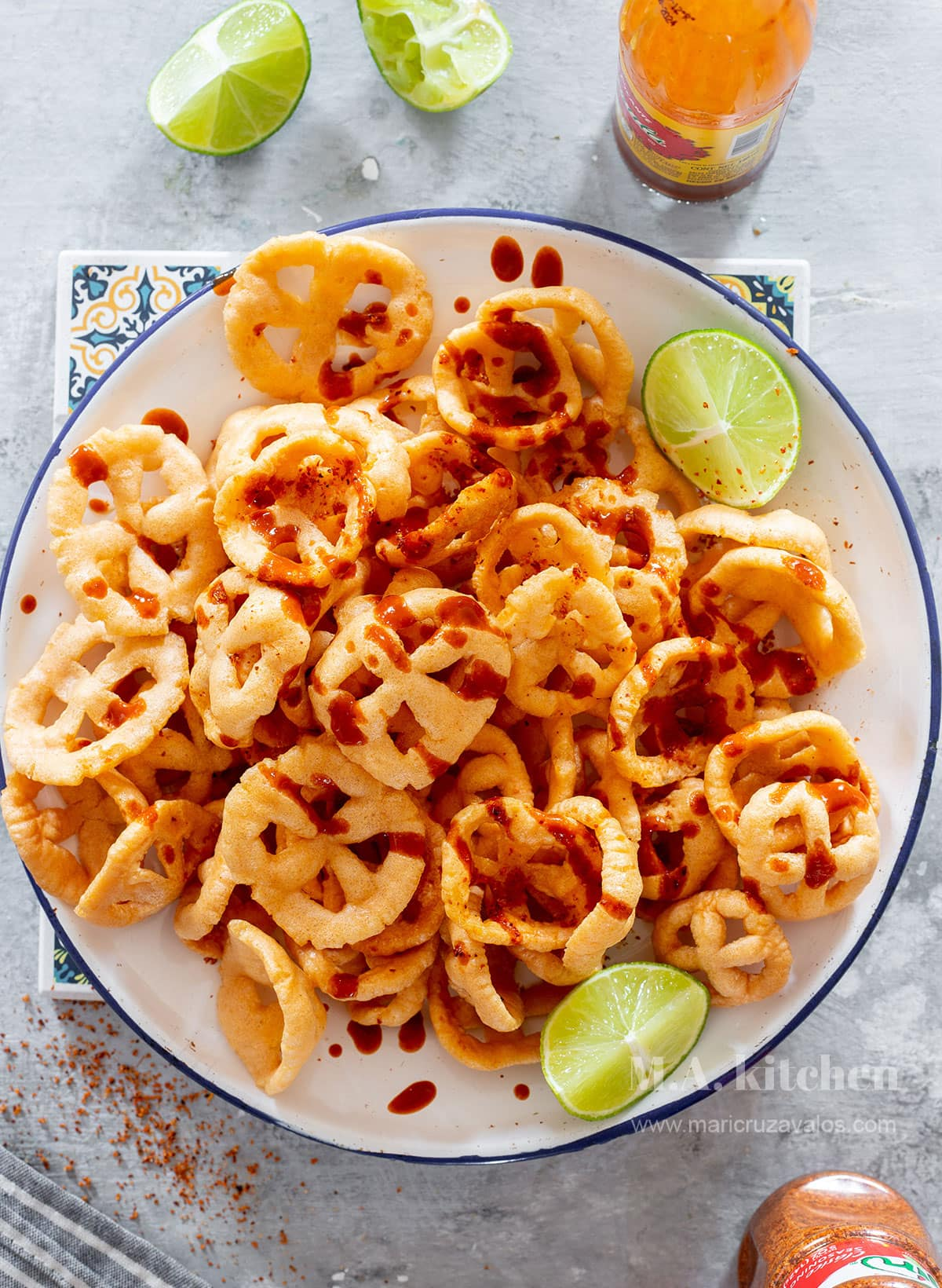 Chicharrones chips on a plate, drizzled with salsa.
