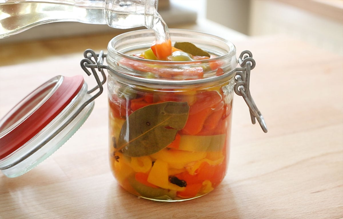 Filling a jar with peppers with vinegar.