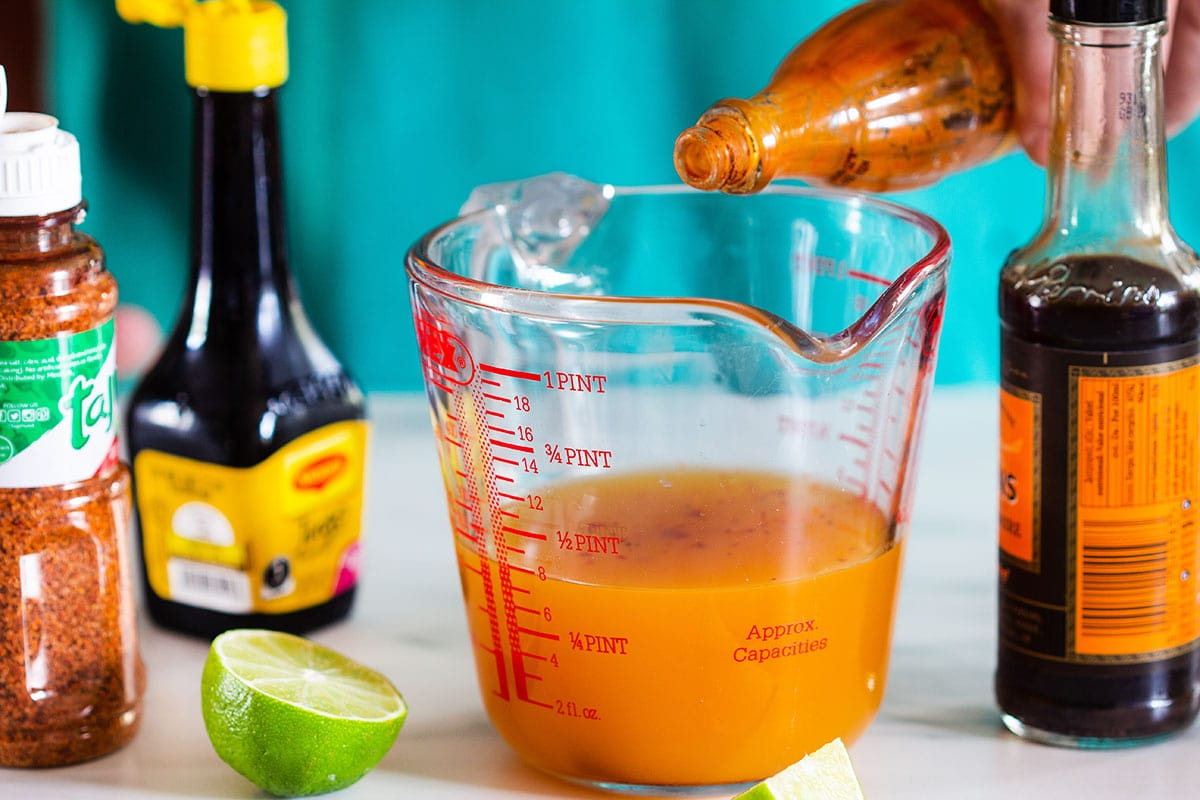 Adding hot salsa to a small pitcher with mango juice.