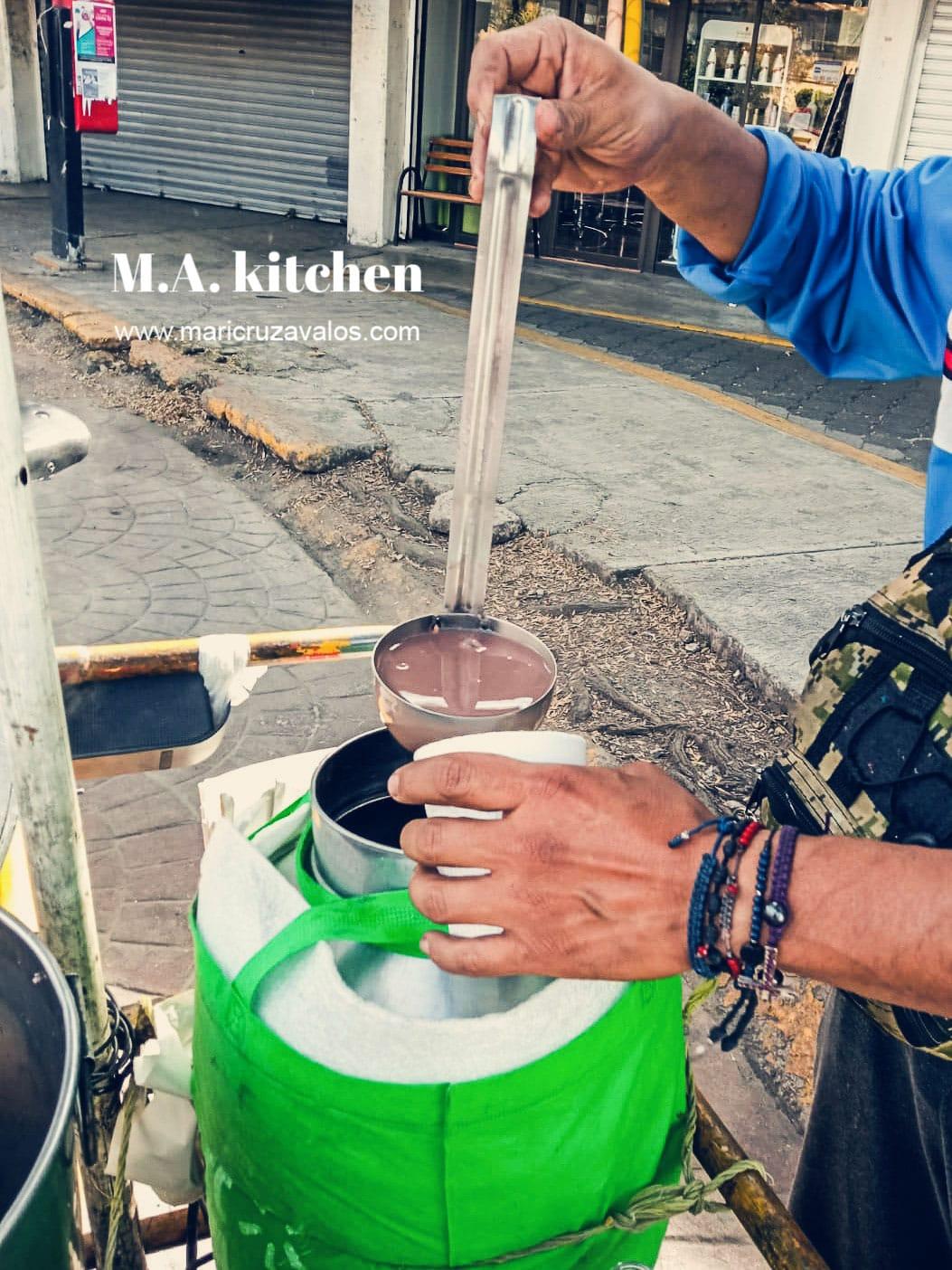 A man serving champurrado in a cup.