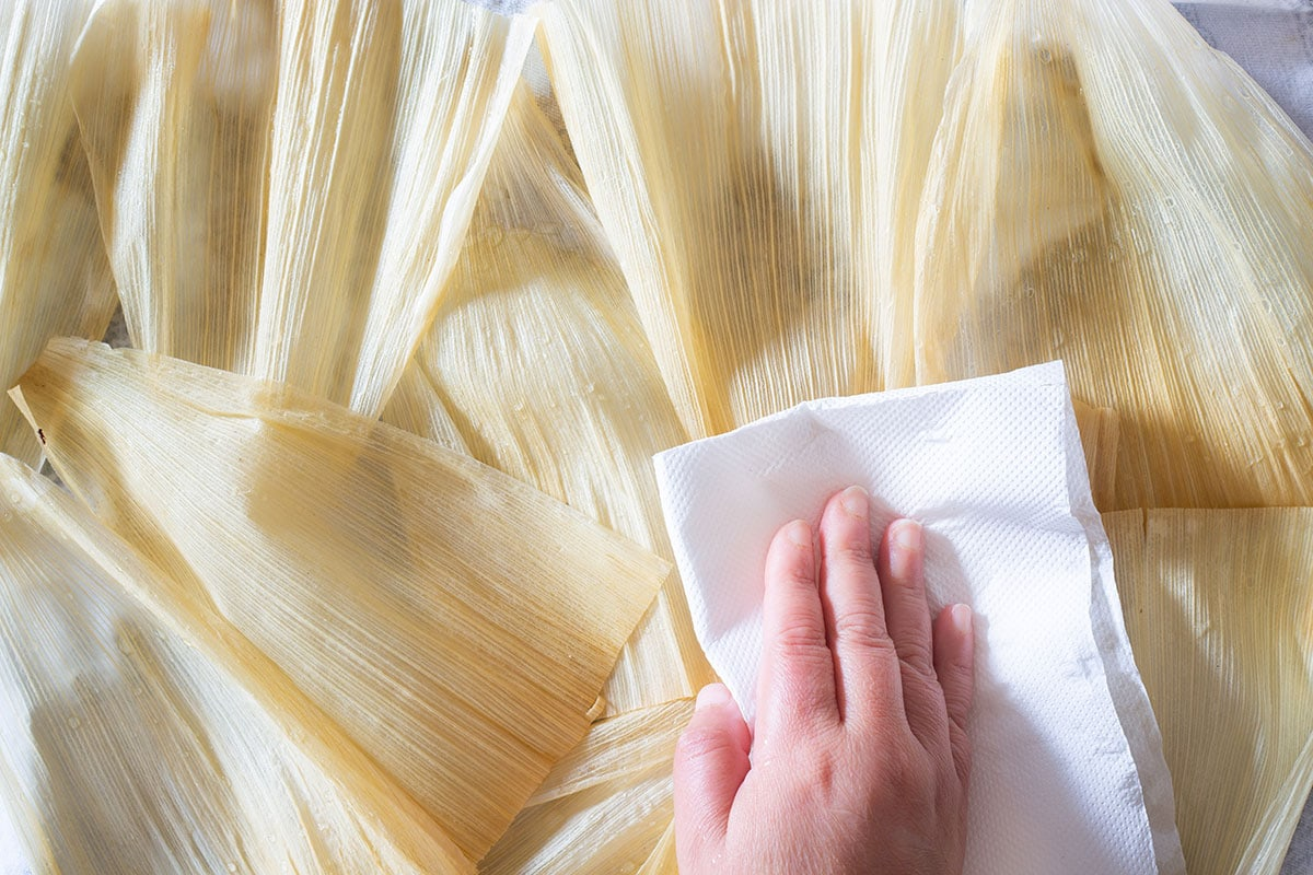 Pat drying corn husks with paper towels.