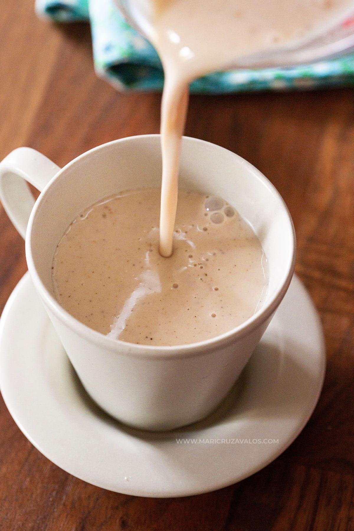 Pouring atole de mazapan in a cup.