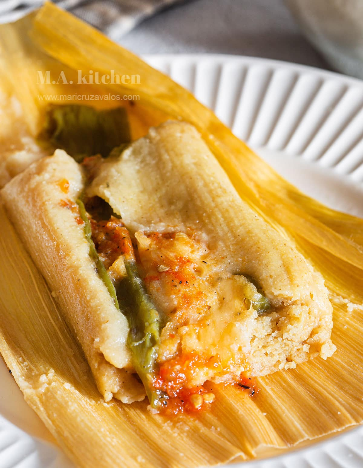 Tamales de rajas close up showing the fluffy and moist texture and the cheese filling.