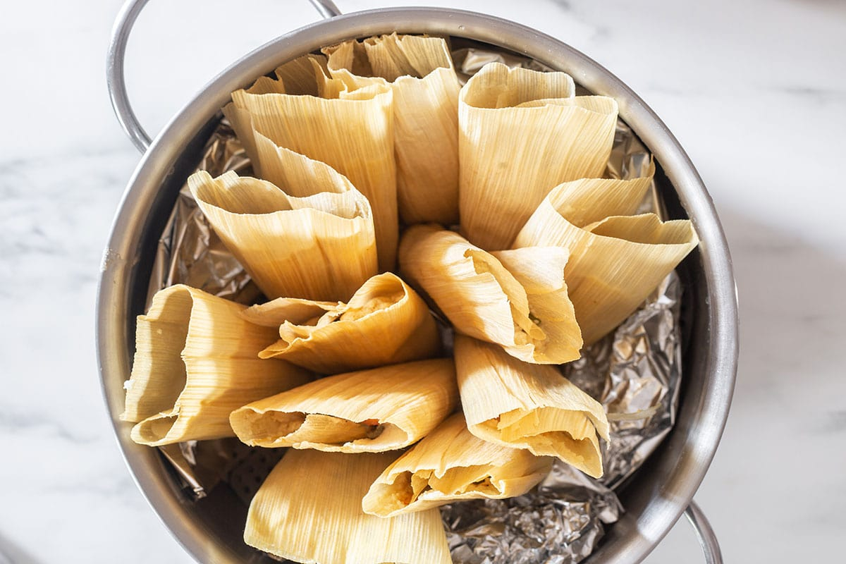 Tamales placed standing up on a steamer.