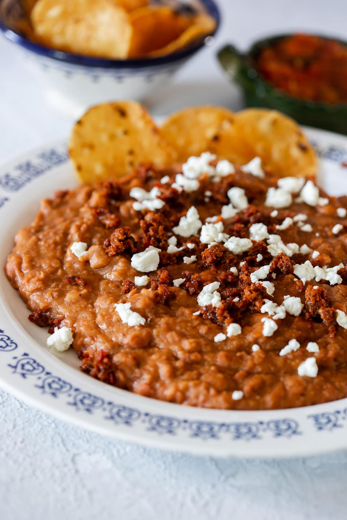 Chorizo and beans served with cheese and totopos.