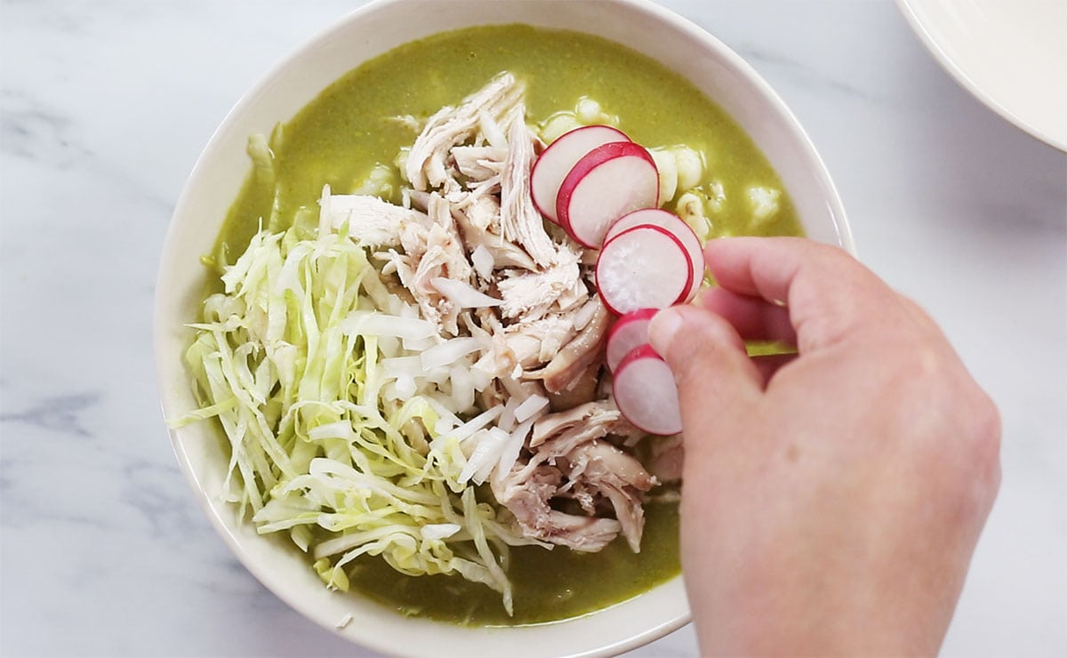 Garnishing pozole verde with various toppings.