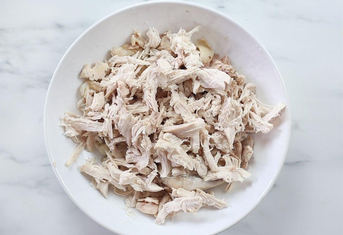 Shredded chicken on a deep plate.
