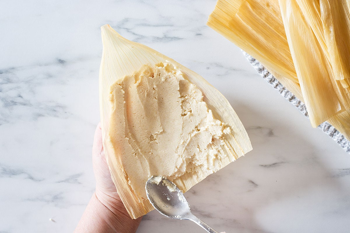 Spreading tamales dough on a corn husk with a spoon.
