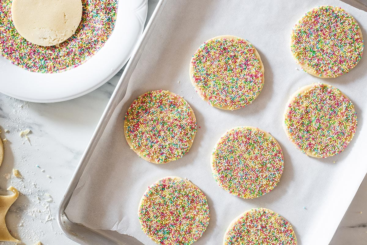Raw sprinkle cookies on a baking sheet.