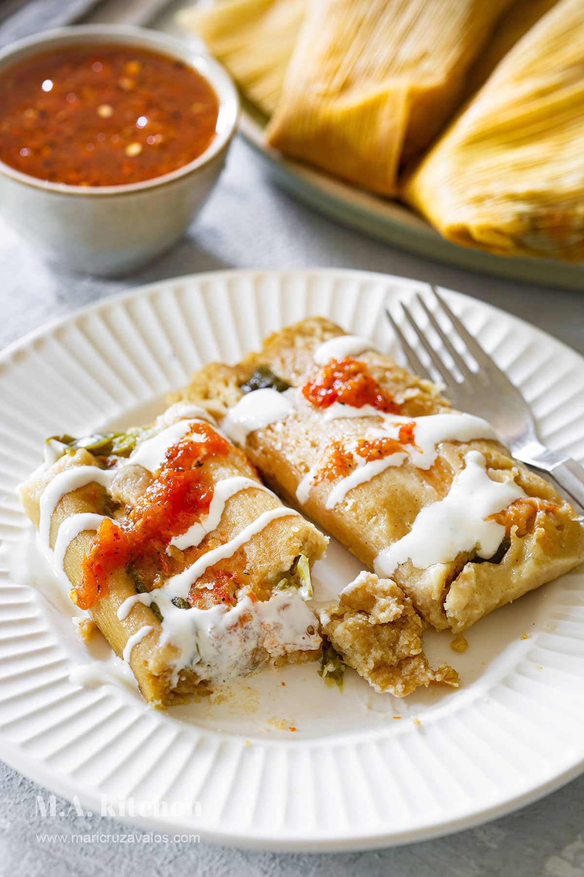 Tamales de rajas served with cream and salsa on top.