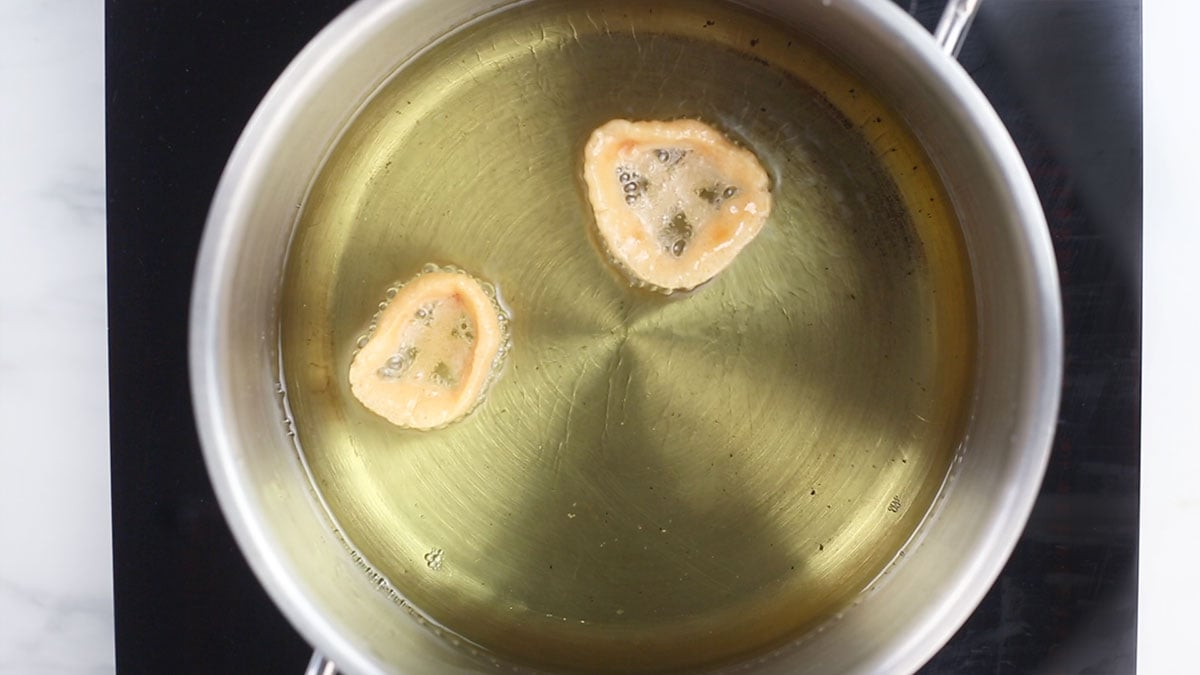 Two duritos frying on oil.