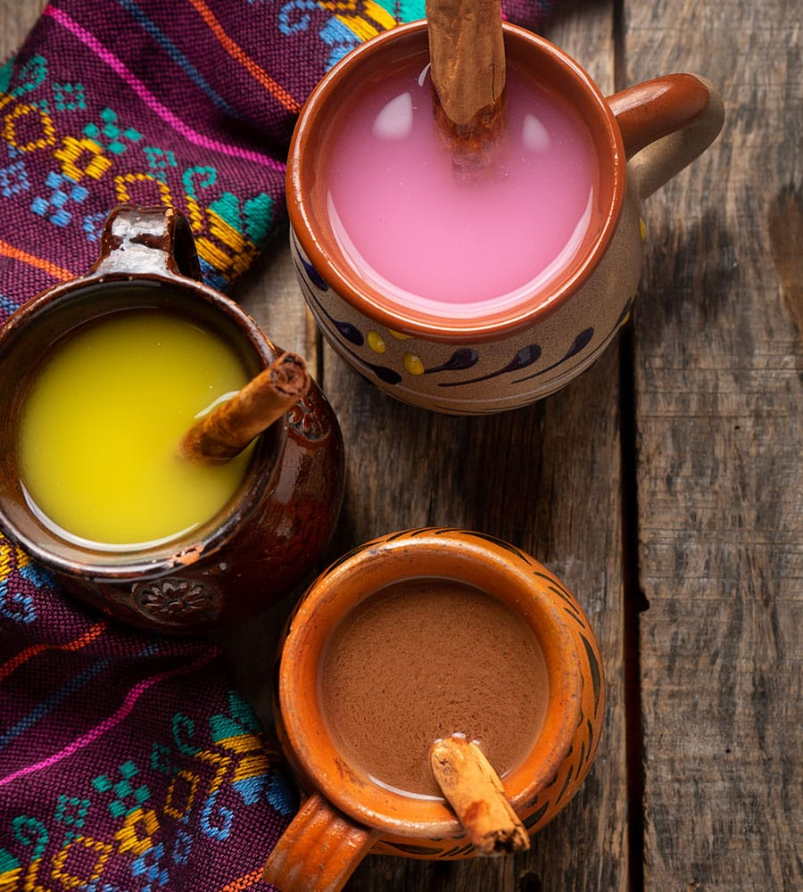 Various flavors of atole served in clay cups.