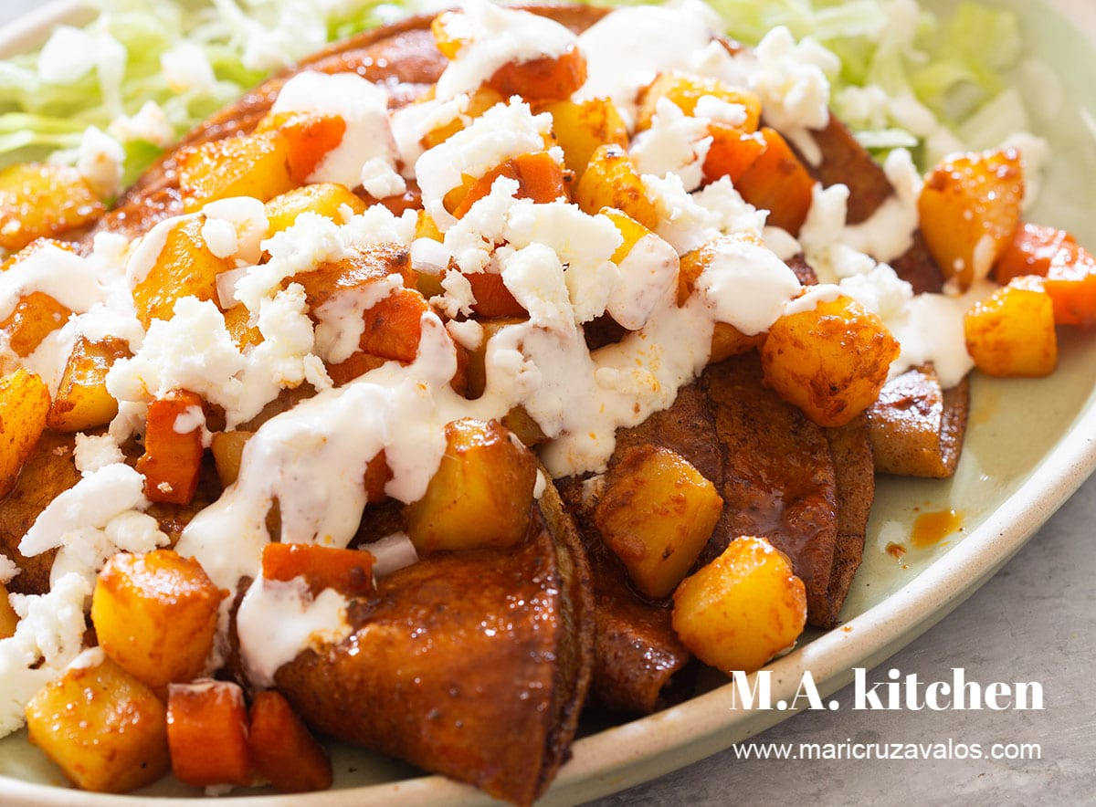 Authentic Mexican enchiladas served with potatoes and carrots.
