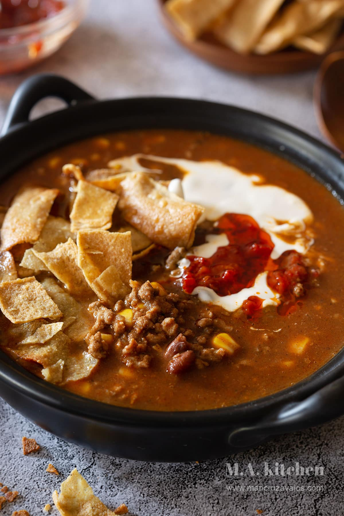 Beef enchilada soup served with tortilla chips, cream and chili oil sauce.
