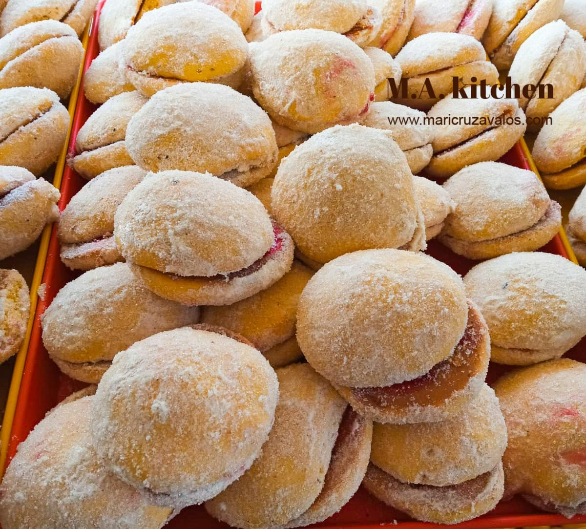 Besos, Mexican pan dulce, piled on a bakery tray.