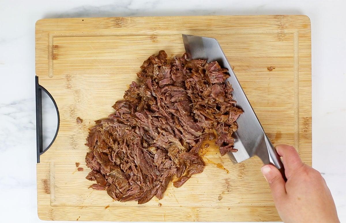 Chopping birria meat in a cutting board.