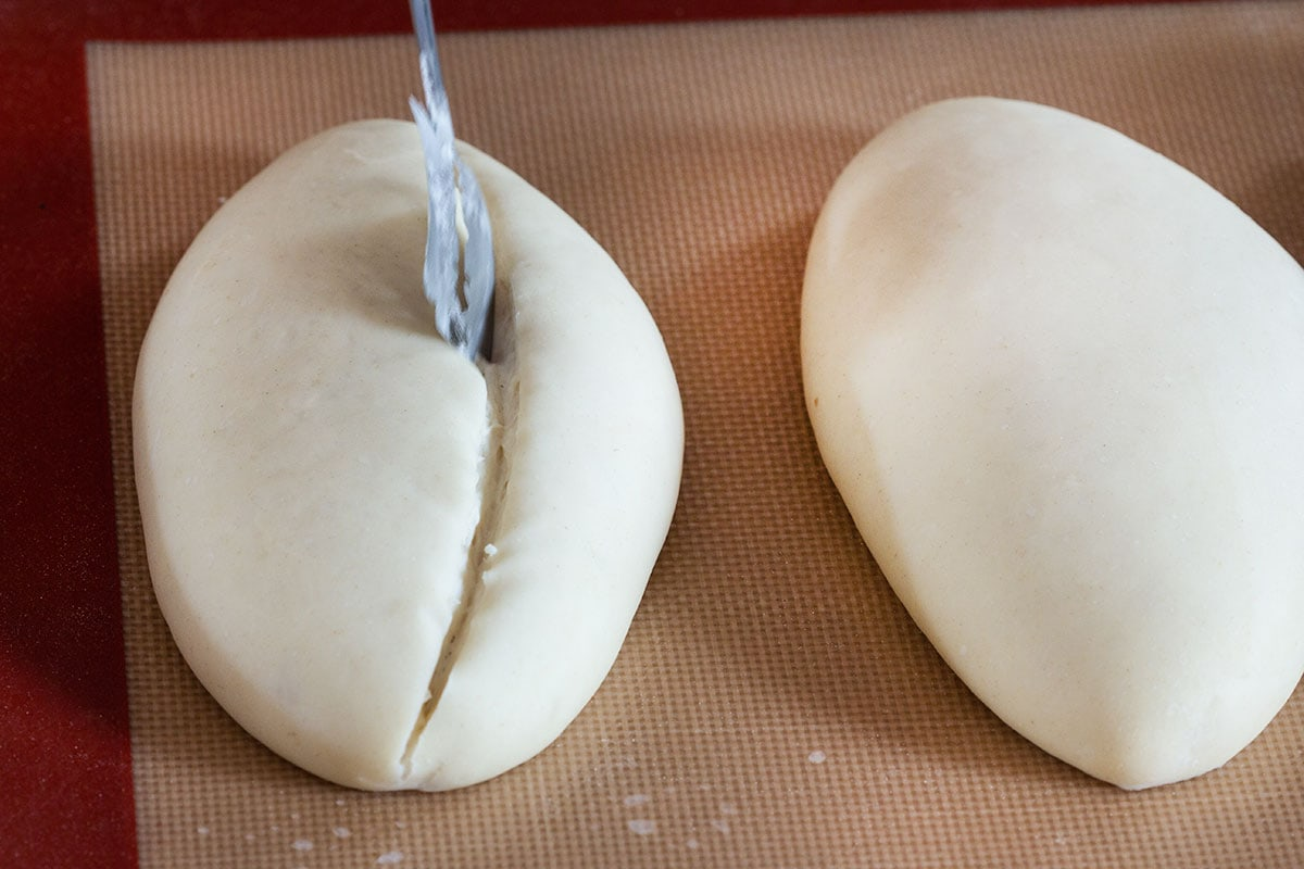 Cutting a raw bolillo just before going into the oven.