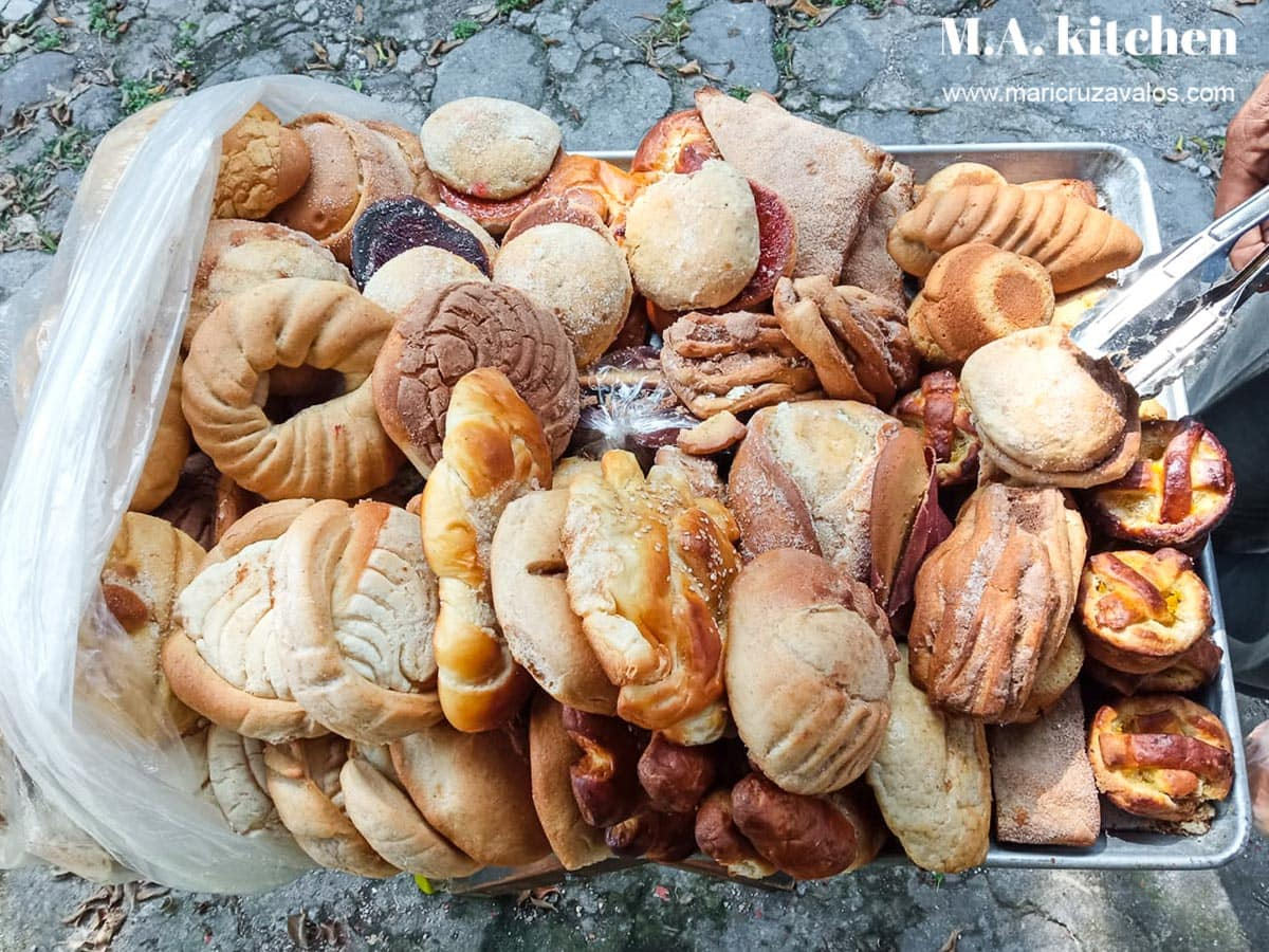 Various types of Mexican sweet bread pan dulce on a tray.