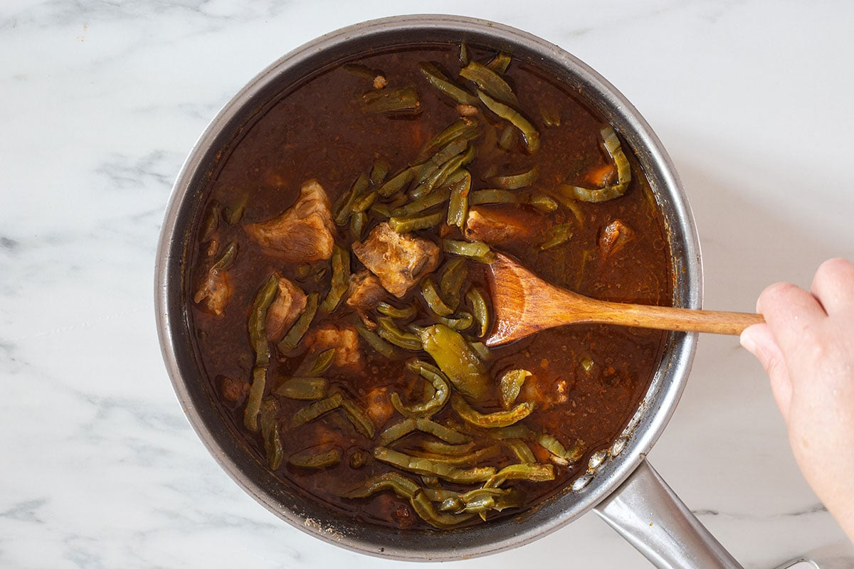 Nopales with pork in chili sauce cooking in a pan.