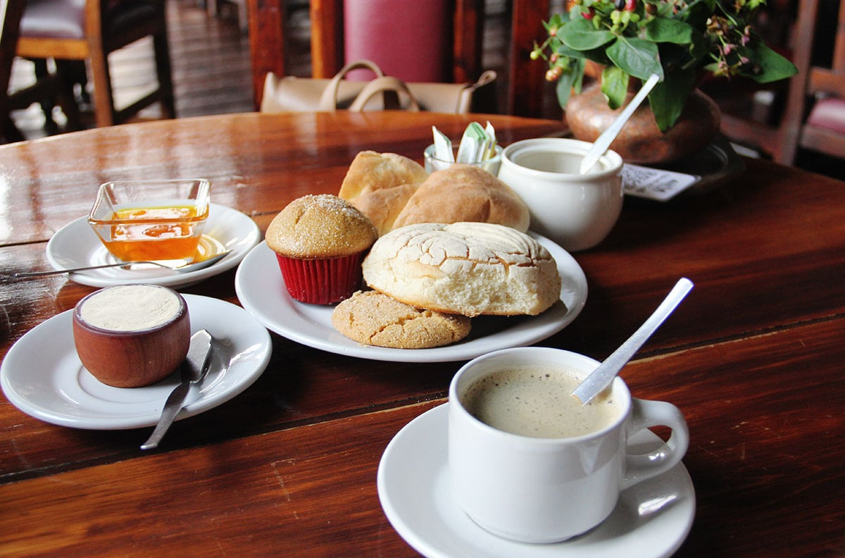 A breakfast table with pan dulce, coffee, milk, hot chocolate and other items.