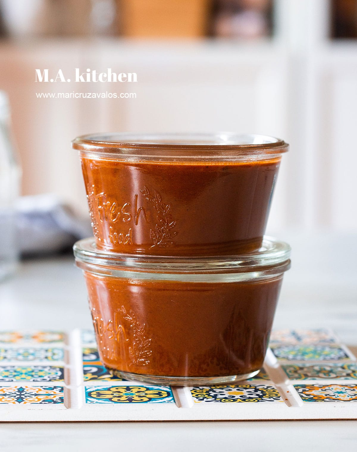Two jars with red enchilada sauce.