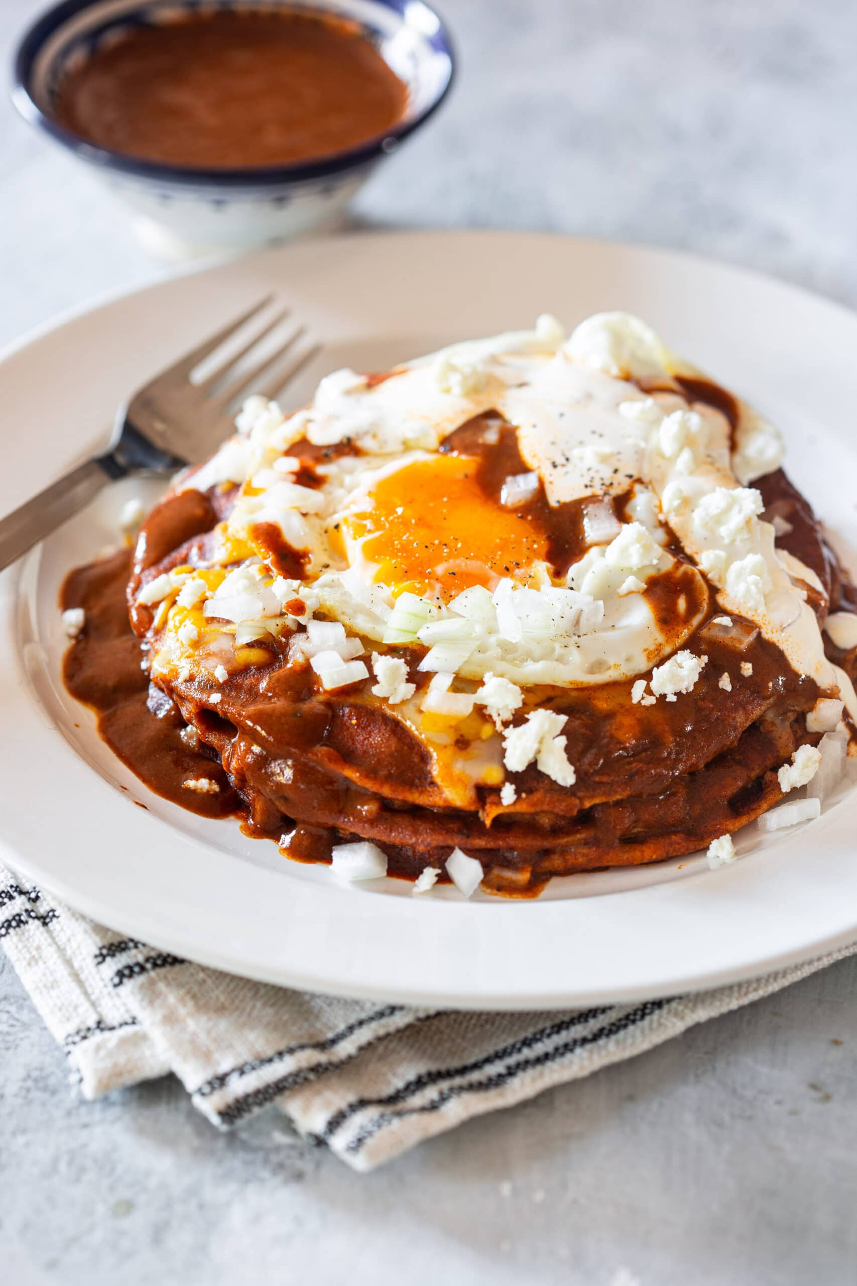 Stacked enchiladas served with a fried egg on top.