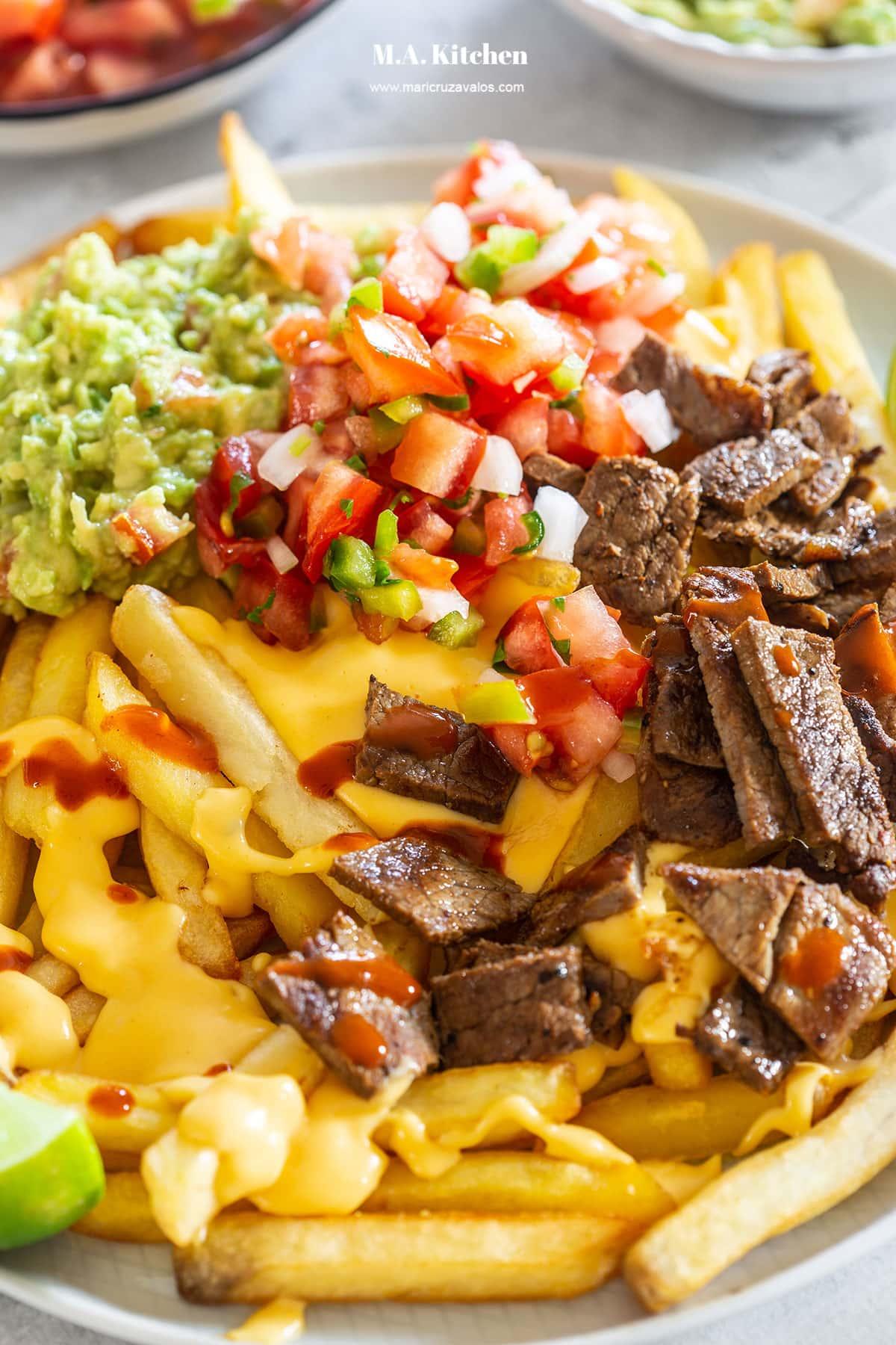 Asada fries topped with guacamole and pico de gallo.
