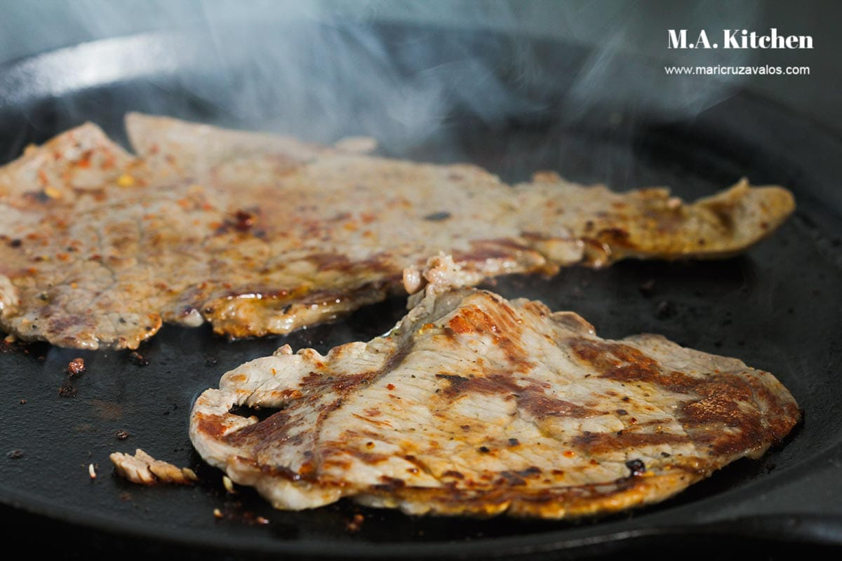 Cooking carne asada in a griddle.