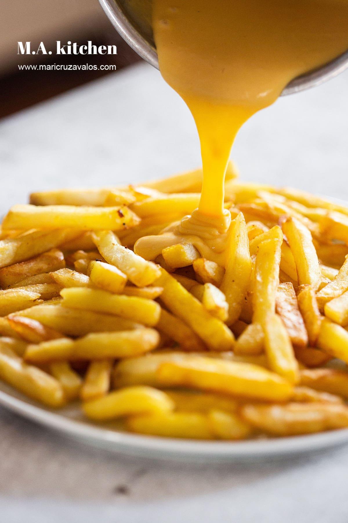 Adding cheese sauce over potato fries.