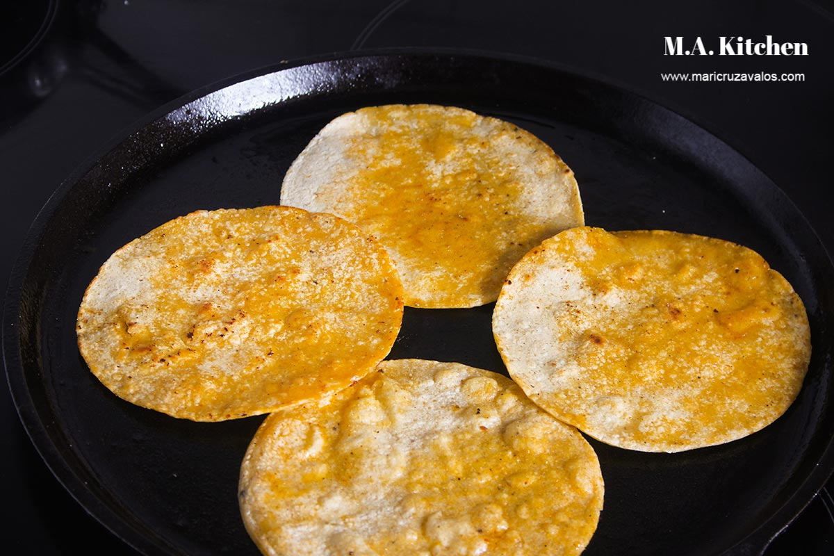 Four tortillas heating in an skillet.