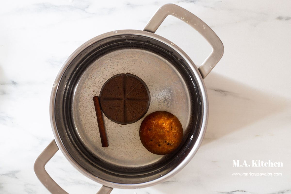 Chocolate, piloncillo and cinnamon added to a pot with water.