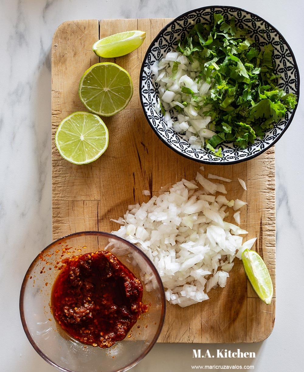 Various toppings for birria tacos displayed on a cutting board.